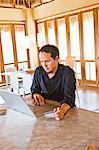 am Laptop zu Hause arbeitender Mann