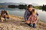 Vater und Sohn schärfen Stock nahe entfernten See