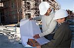 Vorarbeiter und Knabe am Baustelle Blaupausen betrachten