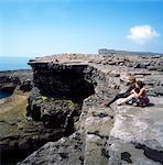 Inishmore, Aran Islands, Co Galway, Ireland; Couple Sitting On The Rocks