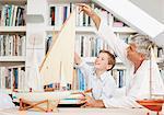 Grandfather and grandson looking at model sailboats