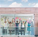 Heureux les gens d'affaires les bras levés à fenêtre couvert de notes adhésives