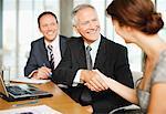 Gens d'affaires souriant serrant la main dans la salle de conférence