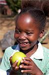 Smiling schoolgirl holding an apple, KwaZulu Natal Province, South Africa