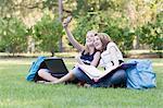Two Girls Doing Homework on Grass