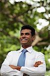 Homme indien en levant et souriant avec bras croisés