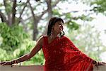 Femme indienne porter le sari rouge, se penchant sur le balcon, souriant
