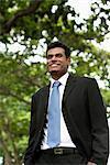 Indien homme souriant à l'extérieur avec des arbres en arrière-plan