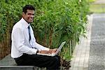 Indien homme assis sur un banc public travaillant sur ordinateur portable et souriant.