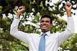 Homme indien avec ses bras levés en souriant à l'extérieur