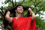 Femme indienne porter le sari rouge sourire avec les mains dans les cheveux