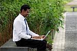 Homme Indien assis à l'extérieur travaillant sur ordinateur portable avec des plantes en arrière-plan