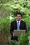 Homme indien sourire lorsque vous travaillez sur ordinateur portable avec des plantes vertes à l'avant-plan et l'arrière-plan