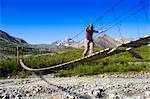 Une femme marche sur un pont suspendu Collège ruisseau Gulkana glacier, centre-sud de l'Alaska, l'été/n