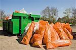 Garbage bags piled beside dumpster