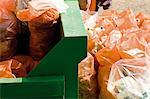 Garbage bags beside full dumpster