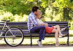 Jeune couple de détente ensemble sur le banc de parc