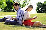 Couple assis dos à dos lecture dans le parc