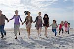 Gruppe von Menschen Hand in Hand und laufen am Strand