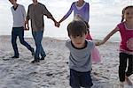 Gruppe von Menschen Hand in Hand und Wandern am Strand