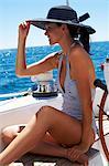Voir le profil:: belle fille assise sur le pont d'un yacht en maillot de bain rayé
