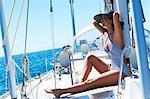 Paysage de belle fille assise sur le pont d'un yacht en maillot de bain rayé