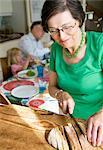 Grandmother slicing bread
