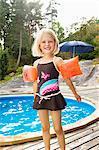 Girl standing beside outdoor pool