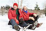 Homme et femme assise à l'extérieur dans la neige