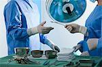 Nurse handing forceps to surgeon in operating room