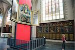Tourist looking at a canvas by Rubens, in Onze Lieve Vrouwekathedraal, Antwerp, Flanders, Belgium, Europe