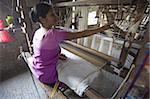 Woman at village silk loom weaving Assam Muga natural undyed silk in Sualkuchi, Assam, India, Asia