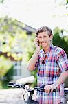 Sourire adolescent avec vélo parlait au téléphone cellulaire