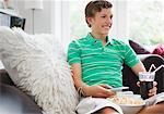 Adolescent avec collations tenant la télécommande