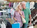 Couple souriant, porter les sacs à vêtements magasin
