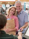 Couple souriant avec sac shopping, carte de crédit pour le chèque de remise