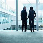 Business people talking near glass wall in office