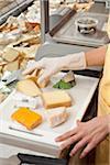 A sales clerk preparing wedges of cheese