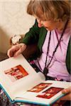 A senior woman looking through a photo album