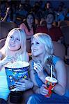 Amis souriants assis dans le théâtre avec pop-corn et soude, regarder film