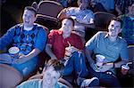 Jeunes hommes inclinables, regarder le film dans le théâtre, le sourire