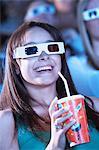 Jeune femme portant 3D lunettes regarder film 3D en théâtre, boire des boissons gazeuses