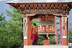 Un moine et une roue de prière sur le chemin vers le monastère de Paro Taktsang dans le royaume himalayen du Bhoutan