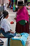 Ecuador, Two women negotiate the price of beads at Otavalo Indian Market.