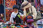 Ecuador, A tourist buys woollen hats from an indigenous Ecuadorian woman at Otavalo market.