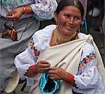 Ecuador, An indigenous Ecuadorian woman busy making a woollen hat at Otavalo market.