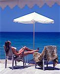 Girl with drink sun-bathing at the beach bar on Boussolos Beach