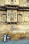 Indien, Rajasthan, Jaisalmer. Leben auf der Straße geht auf die äußeren Wände der Stadt größte Haveli, auf so normal, wie ein Modell zwei junge Schulkinder der Fotograf neben der stark dekorierte Wände begrüssen.