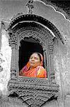 Indien, Rajasthan, einlaufendes, Patwon Ki Haveli. Traditionell gekleidete Dame schaut aus einem stark verzierten Fenster in der in einem erhaltenen Havelis der Stadt.