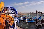 Gens de carnaval de Venise en Costumes et masques de canal avec gondoles et Isola Di San Giorgio Maggiore